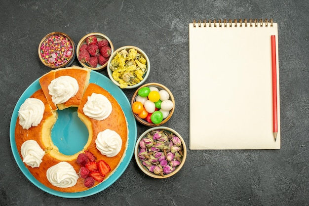 Widok z góry na pyszne kremowe ciasto z kwiatami i cukierkami na czarno