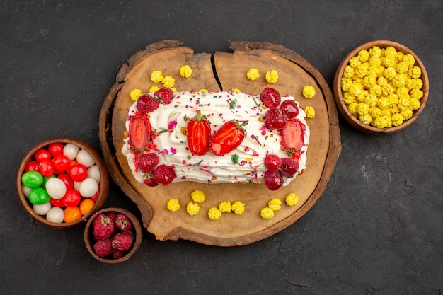 Widok z góry na pyszne kremowe ciasto z owocami i cukierkami na czarno