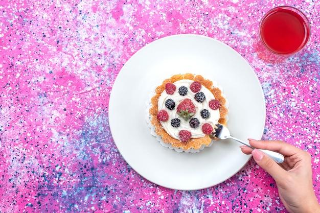 Widok z góry na pyszne kremowe ciasto z różnymi świeżymi jagodami na wierzchu z sokiem na jasnych, świeżych owocach jagodowych