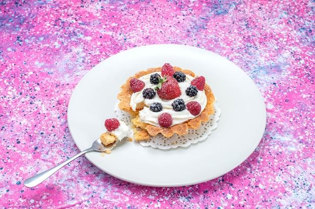 Widok z góry na pyszne kremowe ciasto z różnymi świeżymi jagodami wewnątrz talerza na jasnym biurku, świeże owoce jagodowe
