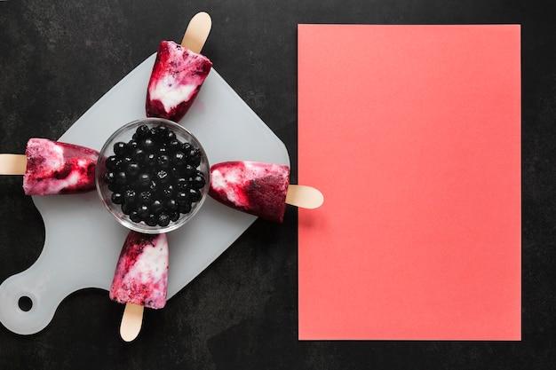 Widok z góry na pyszne lody popsicles z jagodami i miejsce na kopię