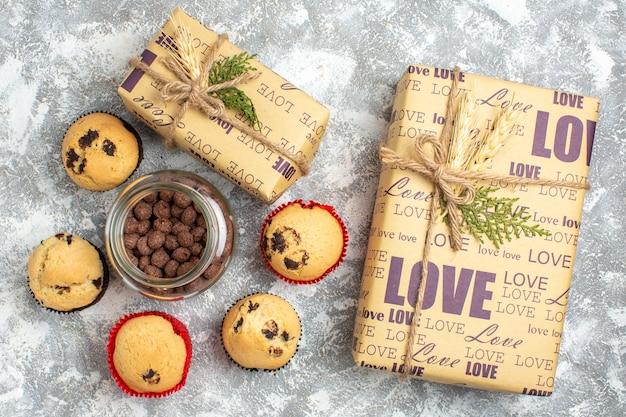 Widok z góry na pyszne małe babeczki i czekoladę w szklanym garnku obok świątecznego prezentu na lodowym stole