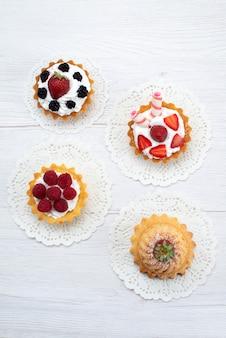 Widok z góry na pyszne małe ciasta ze śmietaną i różnymi jagodami na białym, słodkie ciastka ciastka owocowe