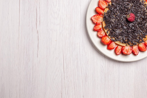 Widok z góry na pyszne naleśniki z truskawkami i kawałkami czekolady na białym stole