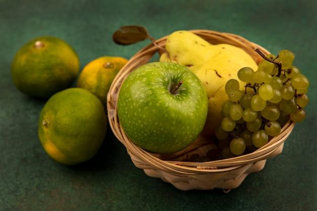 Widok z góry na pyszne owoce, takie jak pigwa jabłkowa i winogrono na wiadrze z mandarynkami na białym tle