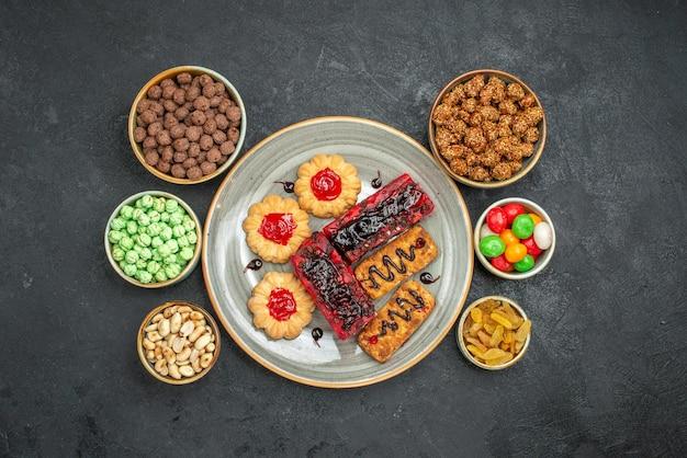 Widok z góry na pyszne owocowe ciasta z ciasteczkami i cukierkami na ciemnym