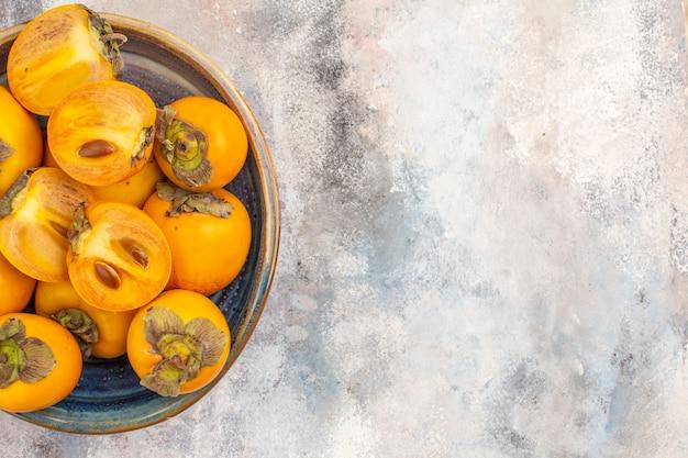 Widok z góry na pyszne persimmons w okrągłym drewnianym pudełku na nagim tle