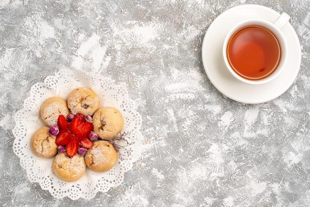 Widok z góry na pyszne piaskowe ciasteczka ze świeżymi truskawkami i filiżankę herbaty na białej powierzchni