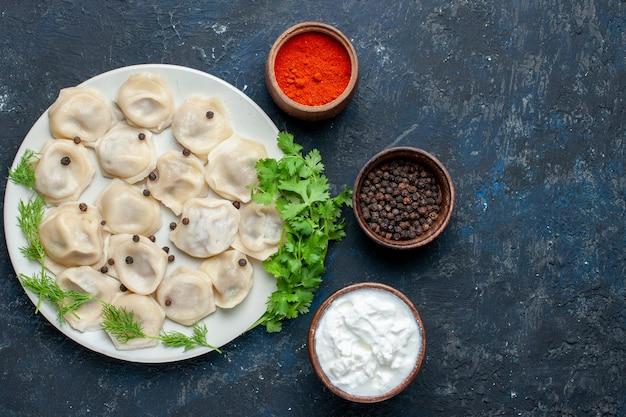 Widok z góry na pyszne pieczone pierogi na talerzu wraz z jogurtem i zieleniną na ciemnoszarym biurku, ciasto obiadowe mięso kaloryczne jedzenie