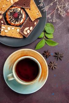 Widok z góry na pyszne plasterki ciasta z filiżanką herbaty na czarno