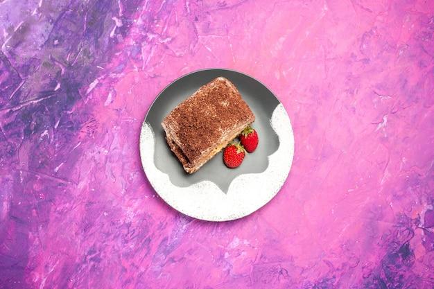 Widok z góry na pyszne słodkie bułeczki z truskawkami na różowej powierzchni