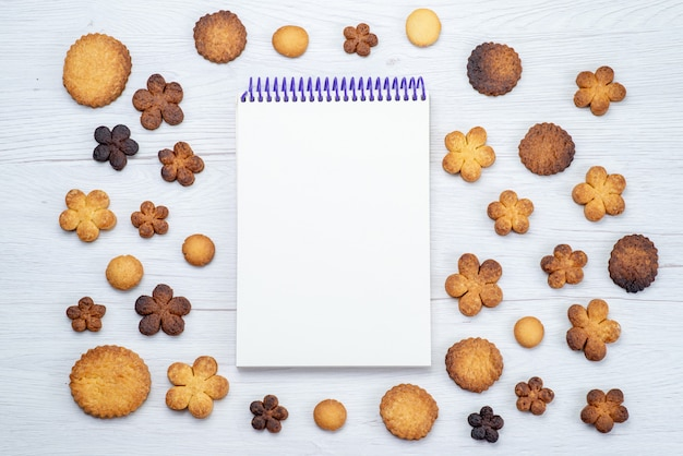 Widok z góry na pyszne słodkie ciasteczka różne uformowane wraz z notatnikiem na lekkim biurku, słodki cukier herbatnikowy