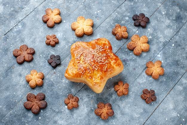 Widok z góry na pyszne słodkie ciasto w kształcie gwiazdy z ciasteczkami na szarym, słodkim cieście do pieczenia