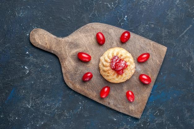 Widok z góry na pyszne słodkie ciasto z czerwonymi dereniami na ciemnoszarym, owocowym biszkopcie
