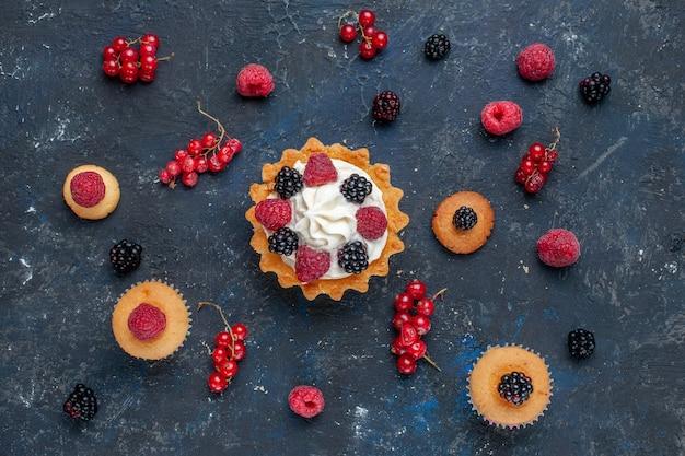 Widok z góry na pyszne słodkie ciasto z różnymi jagodami i pysznym kremem wraz z żurawiną rozłożoną na ciemnym biurku, słodkie ciastko jagodowe