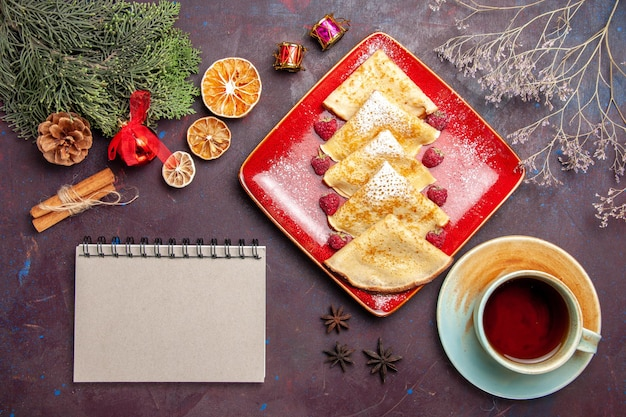 Widok z góry na pyszne słodkie naleśniki z malinami i filiżanką herbaty na czarno