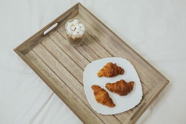 Widok z góry na pyszne śniadanie w łóżku ze świeżo upieczonymi rogalikami z dżemem i kawą na drewnianym stole