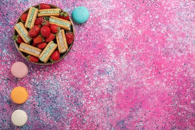 Widok z góry na pyszne waflowe ciasteczka ze świeżymi czerwonymi truskawkami i francuskimi makaronikami na różowej powierzchni