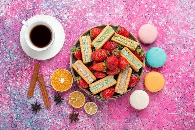 Widok z góry na pyszne waflowe ciasteczka ze świeżymi czerwonymi truskawkami i makaronikami na jasnoróżowej powierzchni