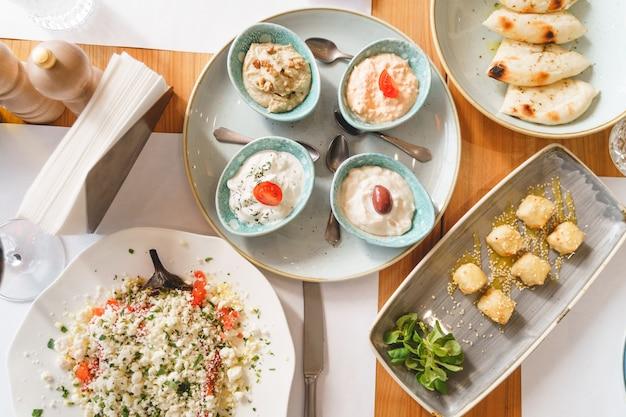 Widok z góry na pyszne zdrowe jedzenie, sosy, łyżeczki, nóż i serwetki na stole w restauracji