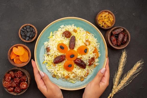 Widok z góry na pyszny gotowany ryż plov z różnymi rodzynkami wewnątrz talerza na szarej powierzchni