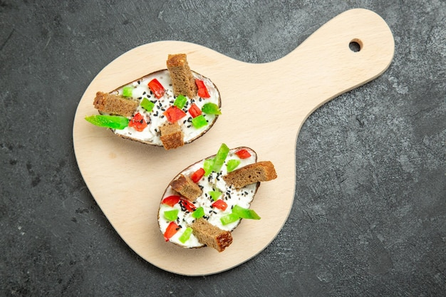 Widok z góry na pyszny posiłek z awokado ze śmietaną pokrojoną papryką i kawałkami chleba na szarej powierzchni