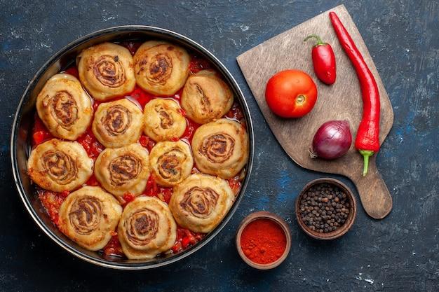 Widok z góry na pyszny posiłek z ciasta z mięsem na patelni wraz ze świeżymi warzywami, takimi jak cebula, pomidory na ciemnoszarym biurku, posiłek mięsny warzywny