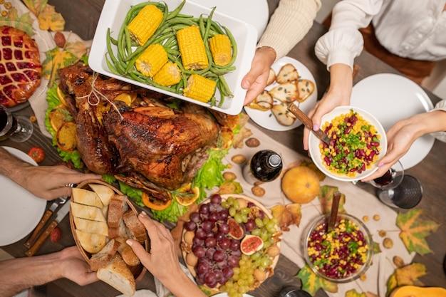 Widok z góry na ręce członków rodziny trzymających talerze ze świeżym pokrojonym chlebem, sałatką i pieczoną kukurydzą i zieloną fasolką nad stołem dziękczynienia