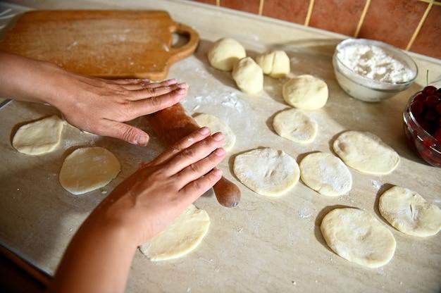 Widok z góry na ręce kobiece kucharz piekarz toczenia ciasta wałkiem do ciasta na blacie kuchennym, aby zrobić okrągłe formy do pierogów. proces gotowania pierogów krok po kroku