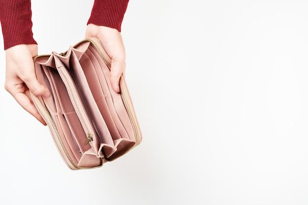 Widok z góry na ręce kobiety trzymając otwarty pusty portfel. bankructwo. bezrobocie. brak gotówki w skórzanej kieszeni. brak koncepcji pieniędzy. styl makiety. na białym tle.