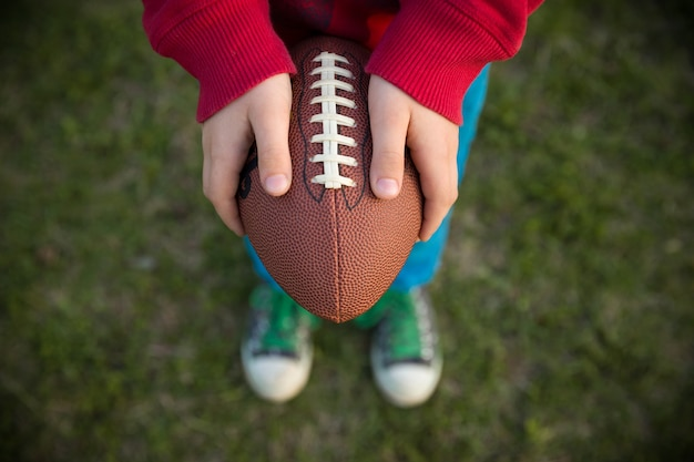 Widok z góry na ręce małego chłopca trzymającego piłkę nożną na stadionie w słoneczny dzień