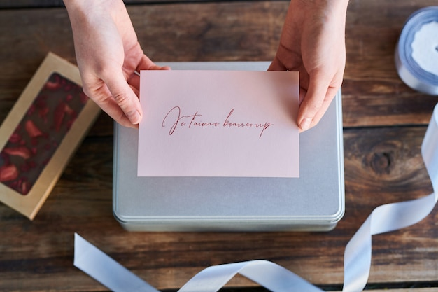 Widok z góry na ręce trzymające kartkę z życzeniami z francuskim zwrotem, co oznacza, że kocham cię bardzo przygotowana na ukochaną