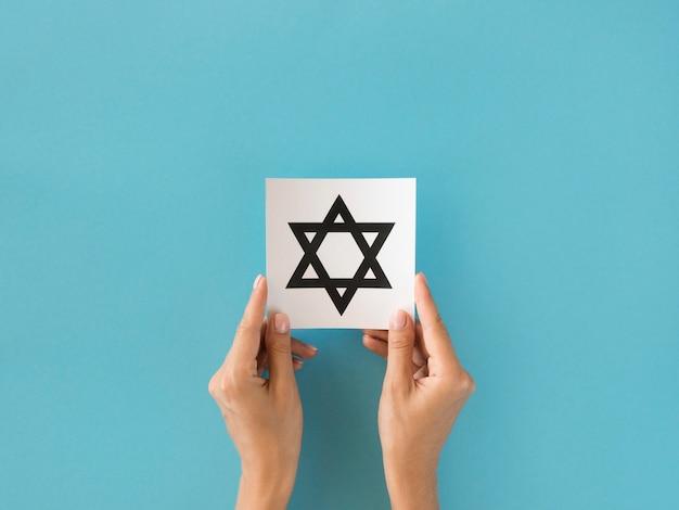 Widok z góry na ręce trzymające symbol gwiazdy dawida