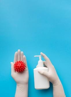 Widok z góry na ręce trzymające wirusa i trzymając butelkę mydła w płynie