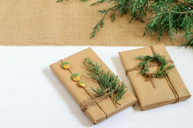 Widok z góry na ręcznie robione prezenty świąteczne owinięte w papier rzemieślniczy z recyklingu, ozdobione gałązkami tui i guzikami.