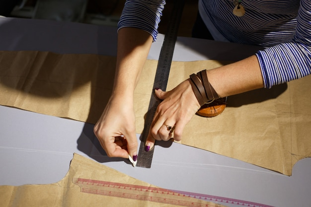 Widok z góry na rękę szwaczki z linijką. mierzy linię cięcia półfabrykatów tkaniny i rysuje mydło. przemysł branżowy