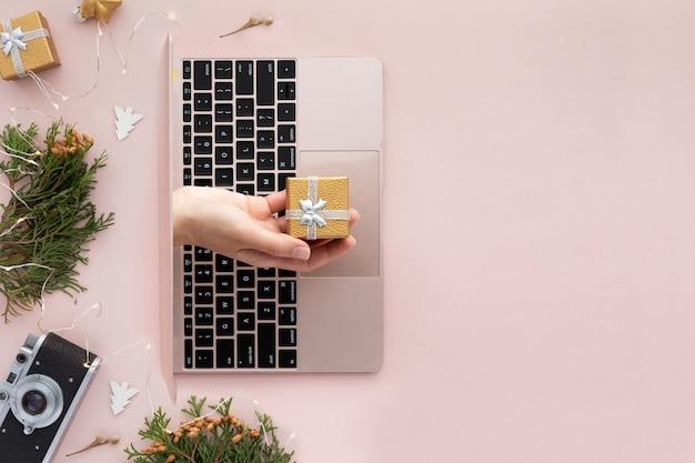 Widok z góry na rękę z prezentem z laptopa. świąteczne mieszkanie leżało na różowym tle