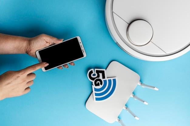 Widok z góry na router wi-fi ze smartfonem i odkurzaczem