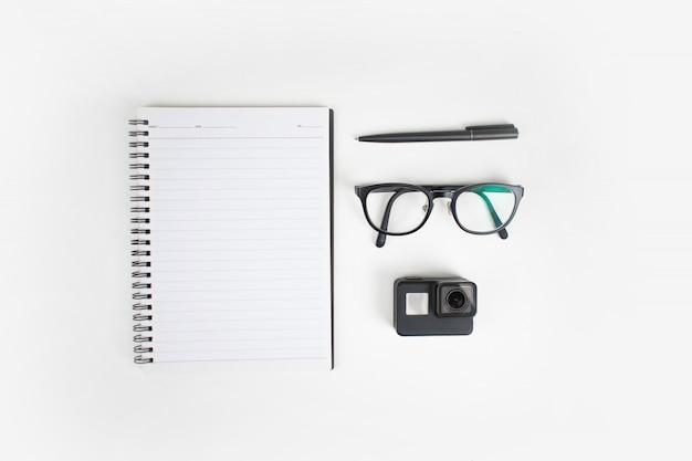Widok z góry na rozmieszczenie notesów, okularów, długopisu i aparatu.