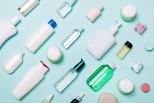Widok z góry na różne butelki kosmetyczne i pojemnik na kosmetyki na niebieskim tle. płaska kompozycja świecka z miejscem na kopię.