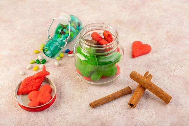 Widok z góry na różne ciasteczka słodkie i pyszne z cynamonem i cukierkami na różowej powierzchni