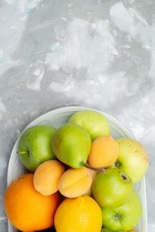 Widok z góry na różne owoce, takie jak cytryny, gruszki, jabłka, winogrona i pomarańcze, na białym biurku wewnątrz talerza z witaminą w kolorze owoców