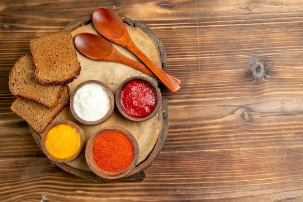 Widok z góry na różne przyprawy z bochenkami czarnego chleba na brązowym stole
