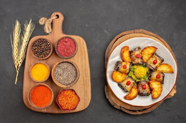 Widok z góry na różne przyprawy z gotowanymi bakłażanami i ziemniakami na czarno