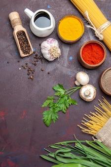 Widok z góry na różne przyprawy z surowym makaronem i grzybami na ciemnej powierzchni surowego produktu żywnościowego