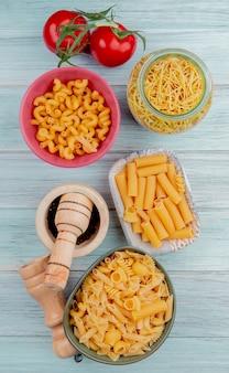 Widok z góry na różne rodzaje makaronów jak spaghetti cavatappi ziti z solą pomidorową i czarnym pieprzem na drewnie