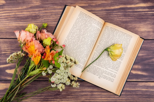 Widok z góry na różne wspaniałe i kolorowe kwiaty z żółtą różą na drewnie