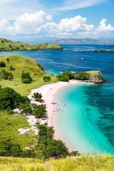 Widok z góry na różową plażę z turkusową czystą wodą na wyspie komodo
