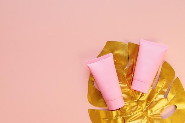 Widok z góry na różową tubkę kremowej makiety ze złotym liściem monstery na różowym tle. niemarkowe opakowanie kosmetyków.