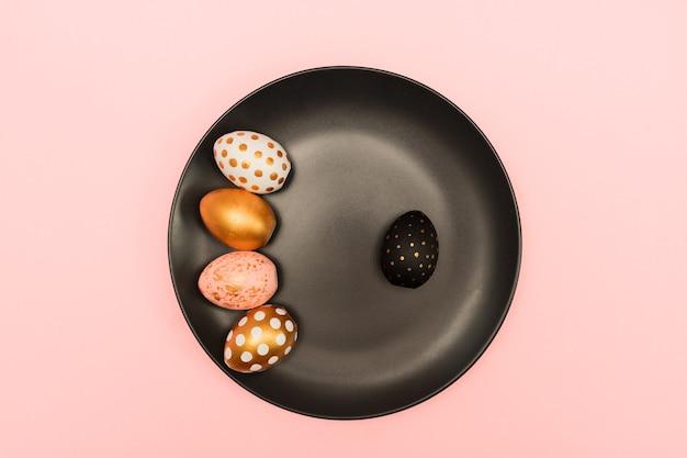 Widok z góry na różowe, białe i złote zdobione jaja wielkanocne na czarnym talerzu na różowym tle. modne tło wakacje.